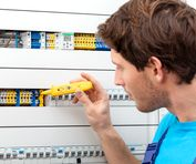 Repairman checking a voltage and fixing a switchboard